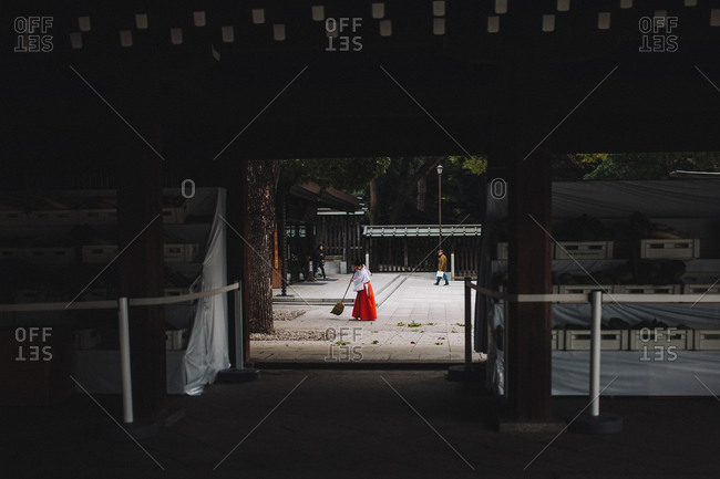 Tokyo, Japan - November 20, 2014: Woman dressed in Japanese traditional dress sweeping at the Meiji Shrine in Harajuku