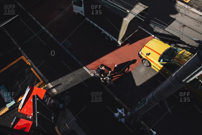 Tokyo, Japan - November 27, 2014: Man riding bike through city traffic in Harajuku