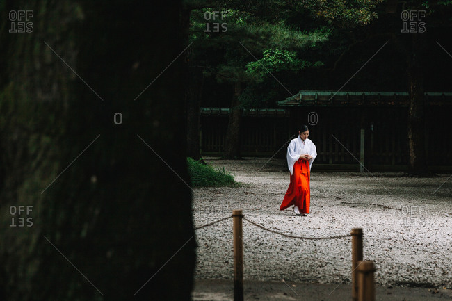 Tokyo, Japan - June 18, 2015: A woman in traditional Japanese dress working at the Meiji Shrine in Harajuku