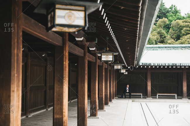 Tokyo, Japan - June 18, 2015: A business man taking a break at the Meiji Shrine in Harajuku