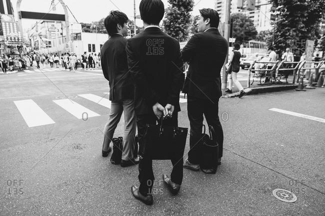 Tokyo, Japan - June 18, 2015: Young professionals standing on Harajuku Street