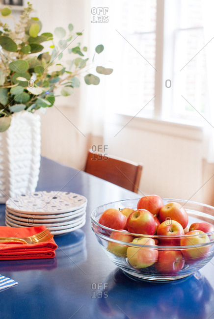 A clear glass bowl full of apples on a dining table