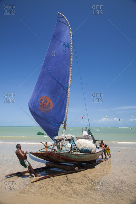 Cumbuco, Brazil - January 3, 2013: Fishermen pulling Jangada fishing boat, Cumbuco, Fortaleza district, Brazil