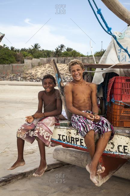 Iguape, Brazil - January 1, 2013: Young local boys sitting on a Jangada fishing boat, Iguape, Fortaleza district, Brazil