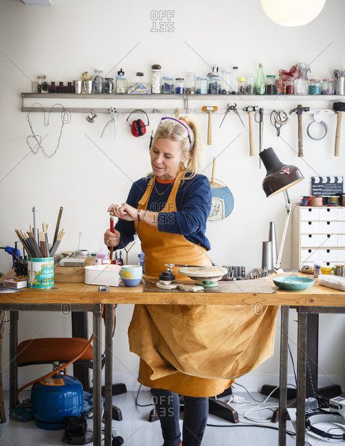 Lofoten Islands, Norway - July 17, 2013: Catrine Linder, a silversmith working at her shop in Henningsvaer village, Lofoten Islands Norway