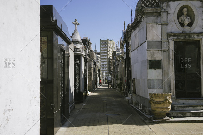 Mausoleums with modern buildings in the distance at La Recoleta Cemetery in Buenos Aires