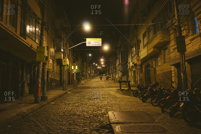 Motorcycles parked on a cobblestone street in Rio de Janeiro at night
