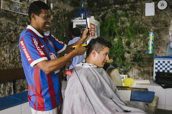 Salvador da Bahia, Brazil - April 20, 2015: Barber cutting a man's hair in a shop in Salvador da Bahia, Brazil