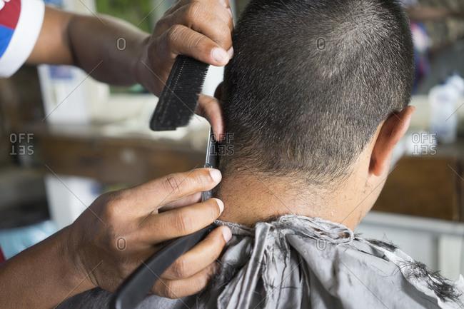 Barber using a straight razor to trim a customer's hair
