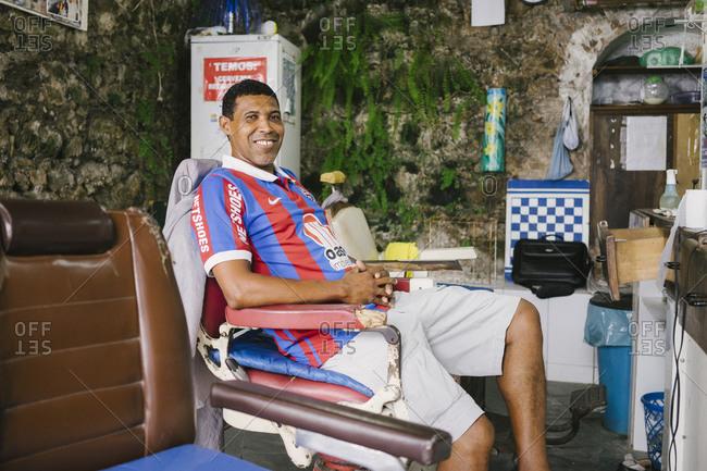 Salvador da Bahia, Brazil - April 20, 2015: Portrait of a man sitting in a barber's chair in a shop in Salvador da Bahia, Brazil