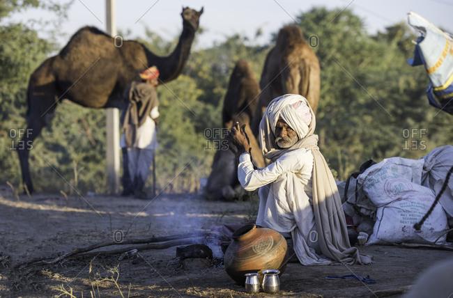 Rajasthan, India - November 18, 2015: Senior man sitting by a fire at the Pushkar Camel Fair, India