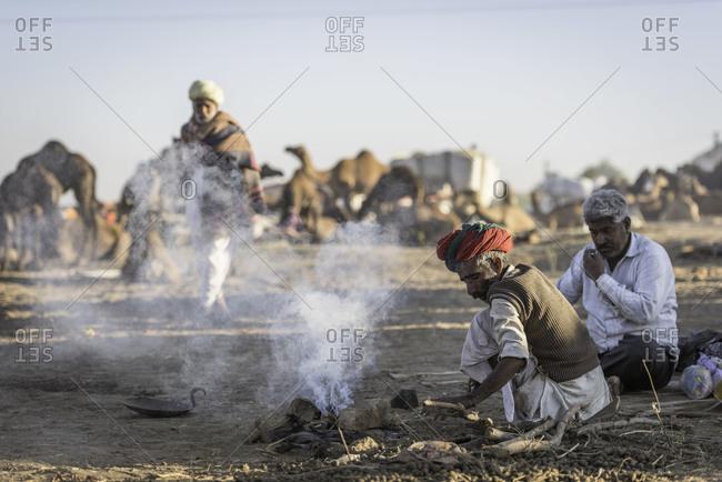 Rajasthan, India - November 18, 2015: Senior men sitting by a fire at the Pushkar Camel Fair, India