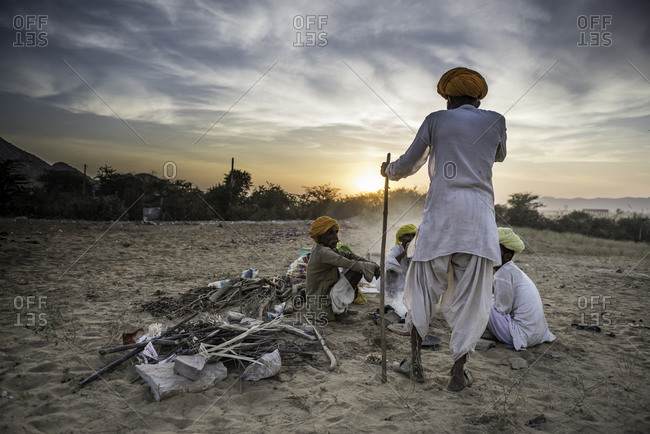 Rajasthan, India - November 18, 2015: Group of Indian men gathered in the sand having a conversation