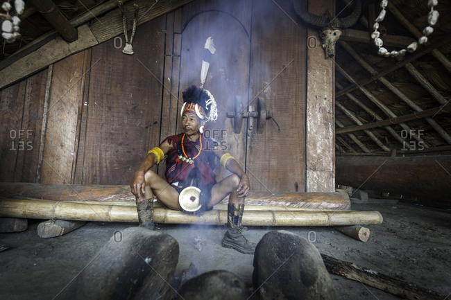 Nagaland, India - December 2, 2015: Indian man in traditional garb sitting near a fire