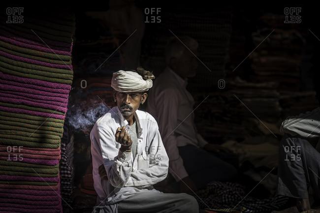 Rajasthan, India - November 18, 2015: Man in an Indian market smoking a cigarette