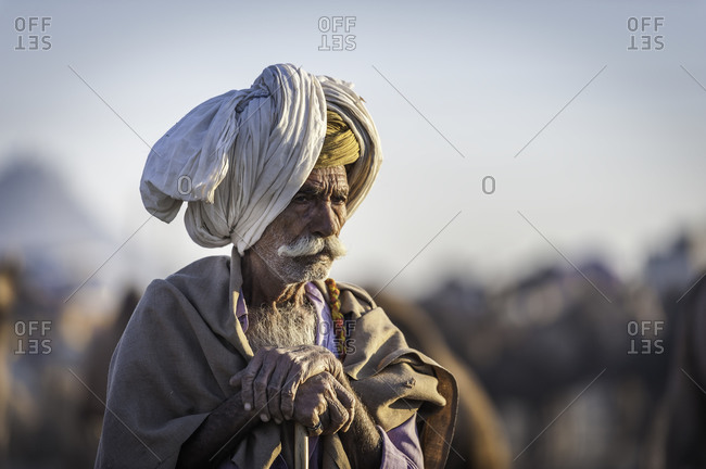 Rajasthan, India - November 19, 2015: Elderly Indian man resting on a wooden walking stick