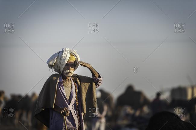 Rajasthan, India - November 19, 2015: Elderly Indian man raising his arm to his face