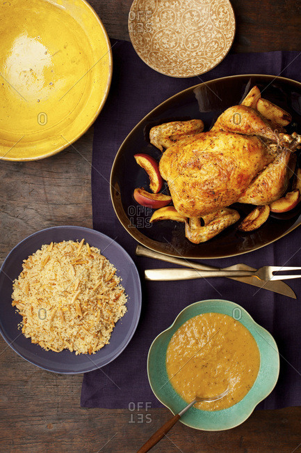 Overhead view of roasted whole chicken, peaches, couscous with almonds and turmeric sauce