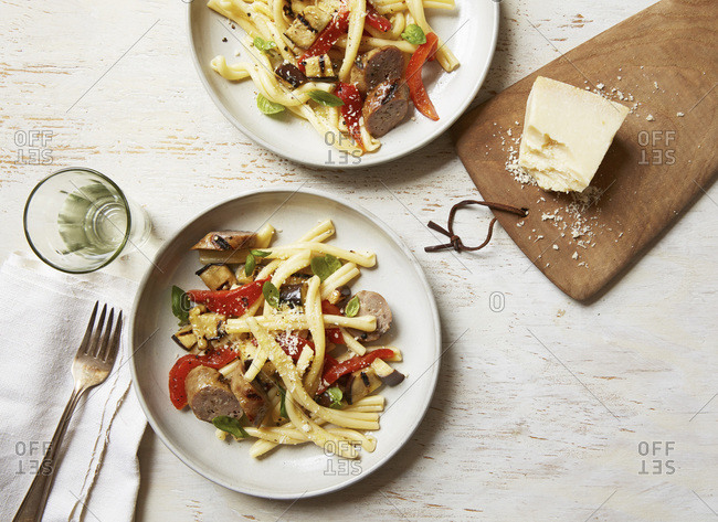 Overhead view of pasta with grilled sausage, peppers and eggplant