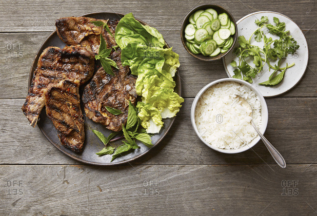 Plate of grilled Sichuan cumin lamb chops with  pickled cucumbers and rice
