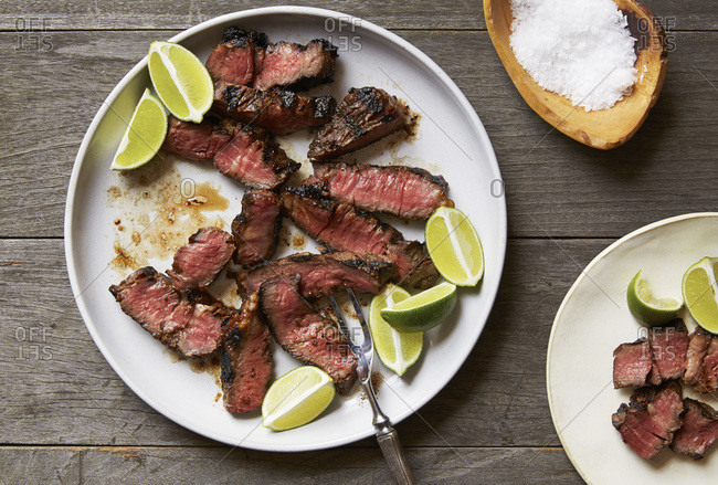 Sliced grilled steak with lime wedges