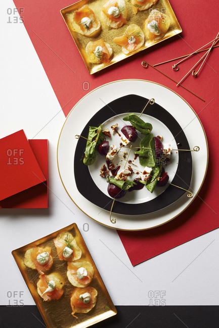 Gourmet appetizers on gold, black and white serving dishes