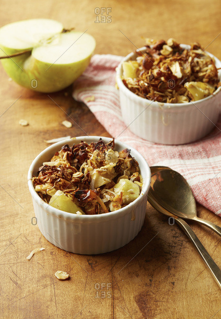 Two dishes of apple  crumble topped with granola