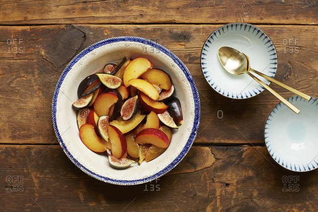 Bowl of sliced figs and plums on wooden table