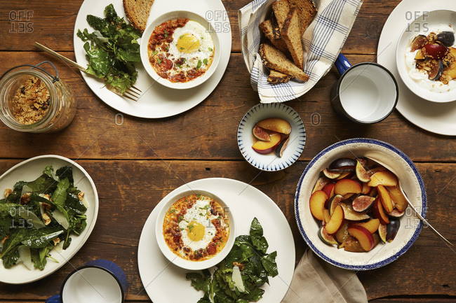 Overhead view of brunch dishes including baked eggs, kale salad, fruit, yogurt and toast