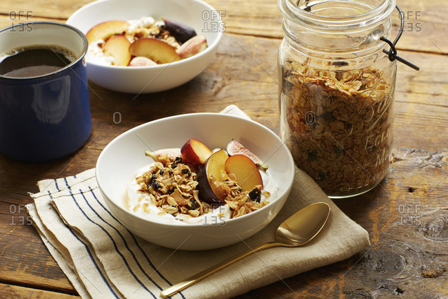 Yogurt topped with sliced figs, plums and granola with coffee for breakfast