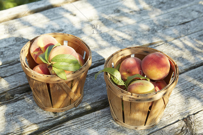 Two baskets of peaches on picnic table