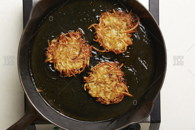Overhead view of latkes frying in skillet