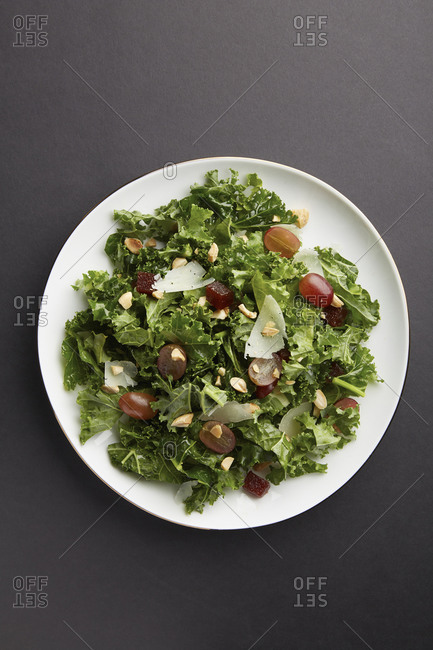 Overhead of kale salad with grapes, shaved cheese, and chopped nuts
