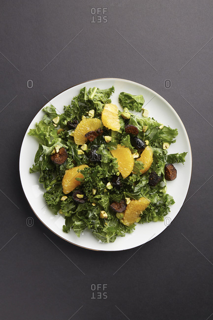 Overhead view of kale salad with mandarin orange sections and figs
