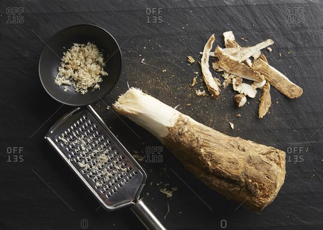 Grating horseradish root into a dish