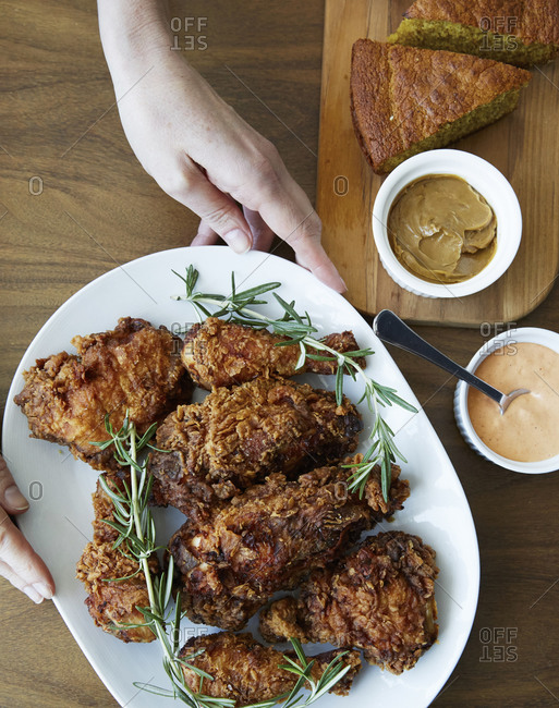 Woman holding platter of fried chicken with rosemary and cornbread