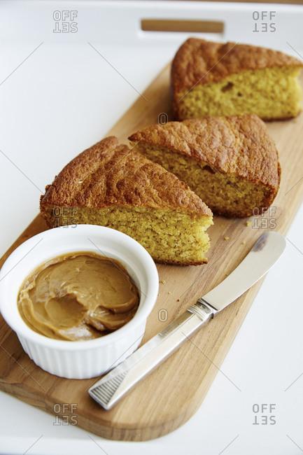 Cornbread on wooden platter with honey butter