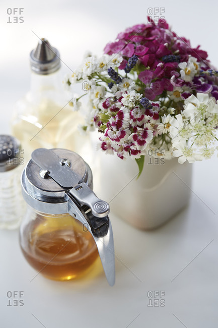 Maple syrup and simple syrup containers next to vase on diner table