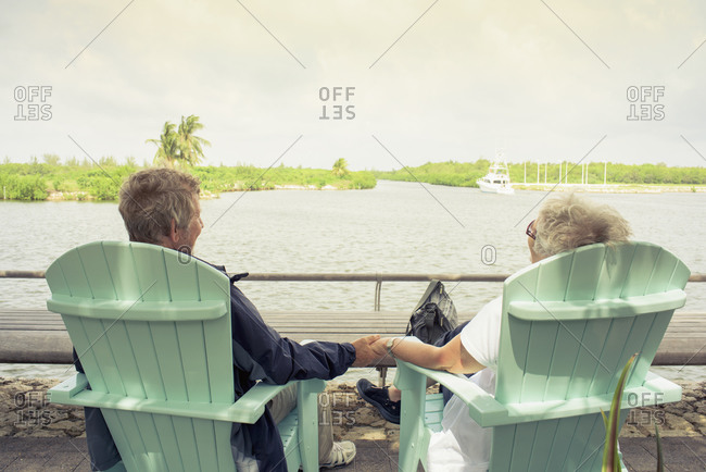 Senior couple holding hands by lake
