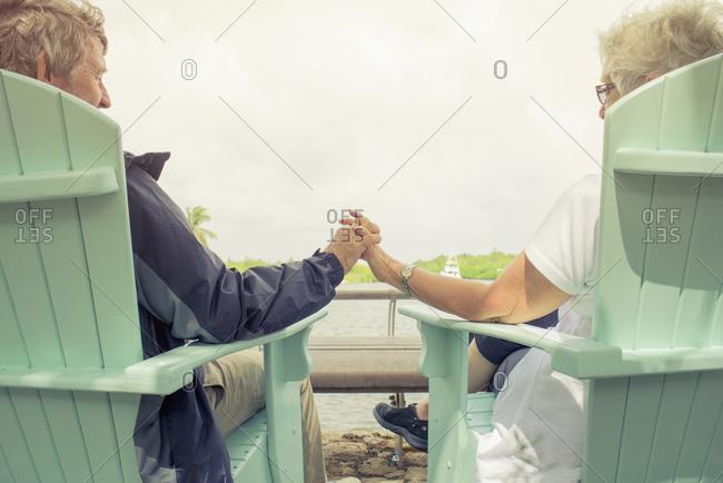Senior couple holding hands at lake