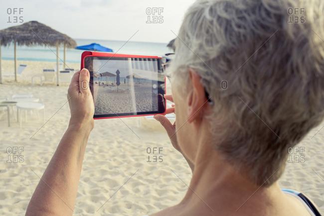 Senior woman taking beach photo