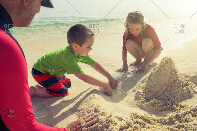 Grandpa and kids playing in sand