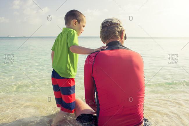 Grandpa and boy sitting in ocean
