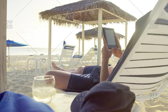 Man reading tablet in beach chair