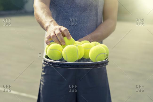 Man balancing tennis balls on racquet