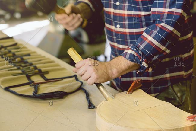 Man shaving piece of wood