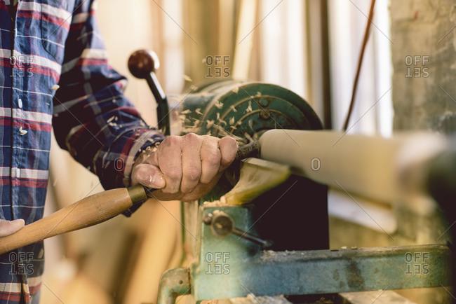 Man carving wood at machine