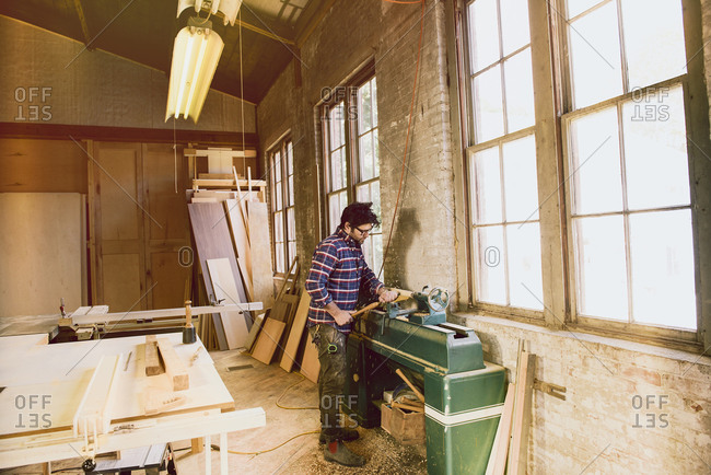 Man shaping a wood piece with machine
