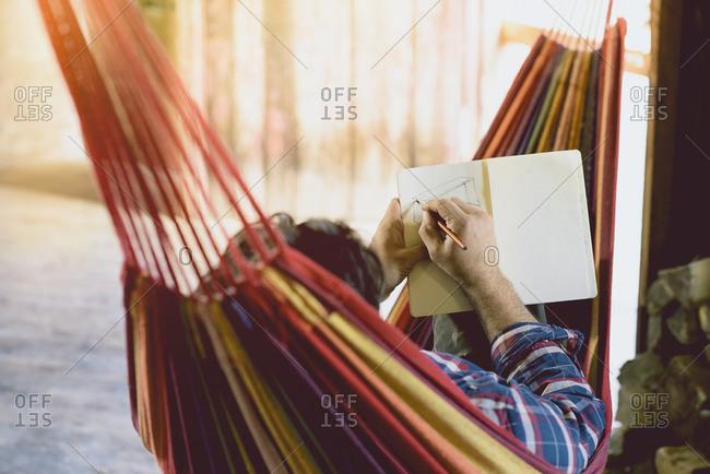 Carpenter in hammock writing
