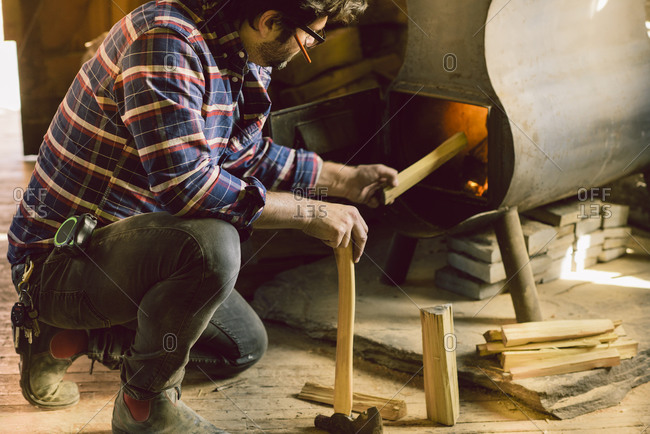 Carpenter putting wood in a stove